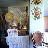 Embroidered linen, baskets and straw hats on table; cheerful and simple, rustic floral mural on chimney flue