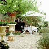 Kaffeepause im Garten - gedeckter Tisch unter Sonnenschirm