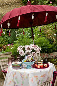 Hydrangeas, fruit, stacked plates and glasses on garden table below parasol