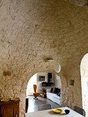 Esszimmer mit Gewölbedecke und Wand aus Naturstein in einem Trullo