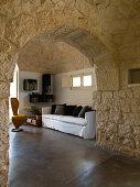 Blick durch Naturstein Rundbogen in ein Wohnzimmer in einem Trullo