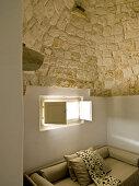 Modernes Sofa unter kleinem Fenster in einem Trullo