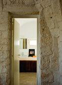 Vorraum mit Naturstein Wand und Blick durch offene Badtür auf modernen Waschtisch
