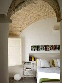 Moderner Metall Stuhl neben Doppelbett vor Wandnische mit Büchern im Schlafraum mit Ziegel Gewölbe