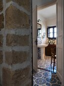 Continuous floor tiling with blue and white pattern in foyer with stone wall and bathroom