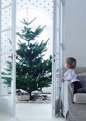 View of Christmas tree through open double doors and child on sofa