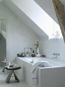 Side table next to bathtub below sloping ceiling
