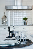Tray of plates and crystal glasses in front of candlesticks on table in country-house kitchen