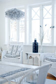 White wicker chairs with cushions next to side table below window in Scandinavian-style living room
