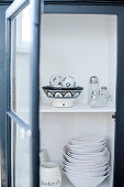 White crockery in open cupboard with glass door