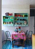 Esstisch mit buntem Wachstuch und pastellgrün lackierte Küchenboards an Wand