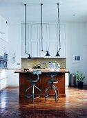 Vintage Hängelampen über Holztheke und Barhocker in offener Küche