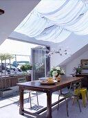 Essplatz unter Dachfenster mit Sonnensegel und offenen Falttüren vor Terrasse
