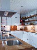 weiße Küche mit Holzarbeitsplatten auf Mittelblock und Unterschränken