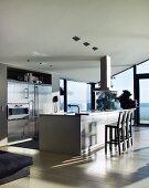 Designerküche mit freistehendem Küchenblock vor verglaster Fensterfront