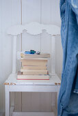 Stack of books on white-painted kitchen chair with carved back against white, wood-panelled wall