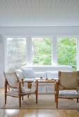 Wood-framed armchairs with canvas upholstery in front of coffee table and sofa below window