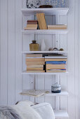 Simple shelves of books on white wooden wall