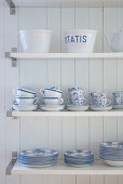 Shelves of white crockery with blue patterns on white, wooden wall