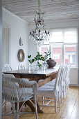 Rustic dining area with white chairs around solid wooden table below crystal chandelier