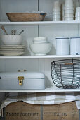Bread box and wire basket on open-fronted, white shelving