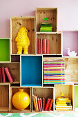 Books and ornaments on DIY shelving made from stacked transport crates, some brightly painted