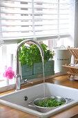 Running water in sink below kitchen window