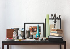 Pewter goblets, vases, stack of books and knick-knacks on modern console table