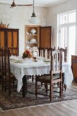 Dark wood, Spanish-style chairs at festively set table in traditional setting