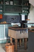 Chopping block side table with integrated knife block in front of simple kitchen counter with plate rack above sink