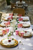 A table laid for a celebration meal outdoors, with coloured wine glasses and plates with a flower design on a white tablecloth