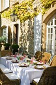 Festively set table on sunny terrace next to Mediterranean country house