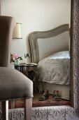 Large mirror with ornate frame on wall of feminine, elegant bedroom