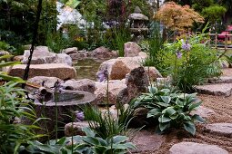 Large stones and grasses on edge of garden pond with Japanese lamp in background