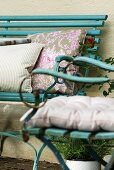 Cushions in various patterns on turquoise bench and garden chair in vintage French country house style