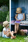 Girl with weaving frame sitting in open-fronted garden shed behind second girl sitting on lawn