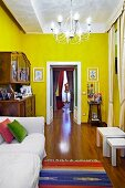 White sofa next to antique dresser and open double doors in yellow-painted interior