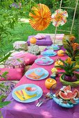 Oriental feast in garden with pastel blue crockery combined with tablecloth and cushions in shades of purple
