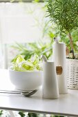 Porcelain vinegar and oil bottles next to salad bowl and rosemary plant