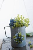 Hydrangea and lady's mantle in metal jug beneath umbrella