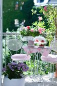Metal chairs and set coffee table with pink floral tablecloth amongst potted plants on romantic balcony
