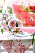 Rosen und Kuchen auf einem kleinen Bambustisch