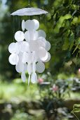 Delicate wind chimes made from white mother-of-pearl discs hanging in garden