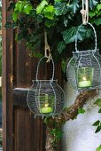 Two green tealight holders in wire baskets hanging in front of ivy-covered house facade
