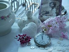 Pocket watch in front of hyacinth bloom, porcelain vessels and antique photograph