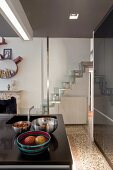 Various dishes on kitchen island in front of modern samba staircase with stainless steel frame