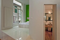 Open-plan sleeping area with white synthetic resin flooring and bed against green-painted wall; view of washstand in bathroom through open door