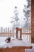 Lantern on snowy terrace table