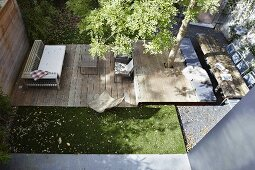 Strip-shaped terrace on several levels with tree growing through deck in sunny urban garden