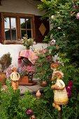 Ceramic figurines in garden and on veranda of farmhouse